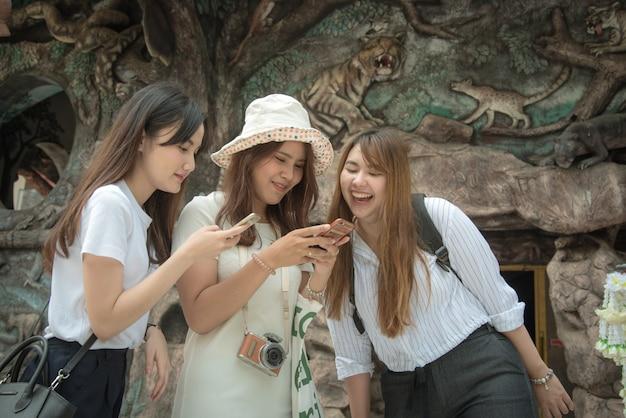 Le donne turisti usano lo smartphone per trovare l'attrazione turistica nel tempio