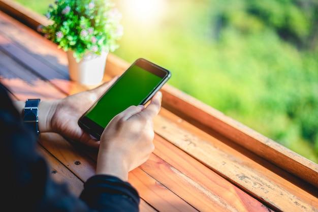 Le donne utilizzano lo smartphone mobile e touch per la comunicazione e il controllo sullo schermo verde