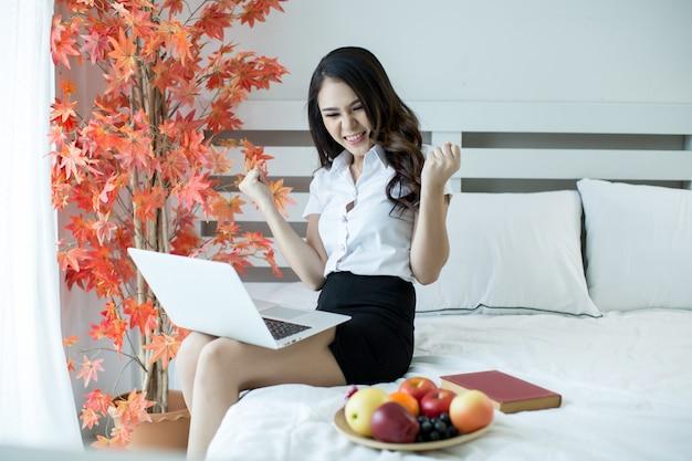 Le donne vestono le uniformi degli studenti stanno guardando un film da un laptop