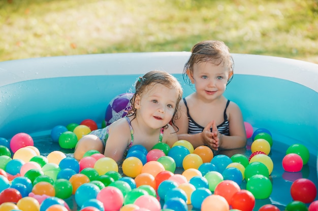 Le due bambine che giocano con i giocattoli in piscina gonfiabile in giornata di sole estivo