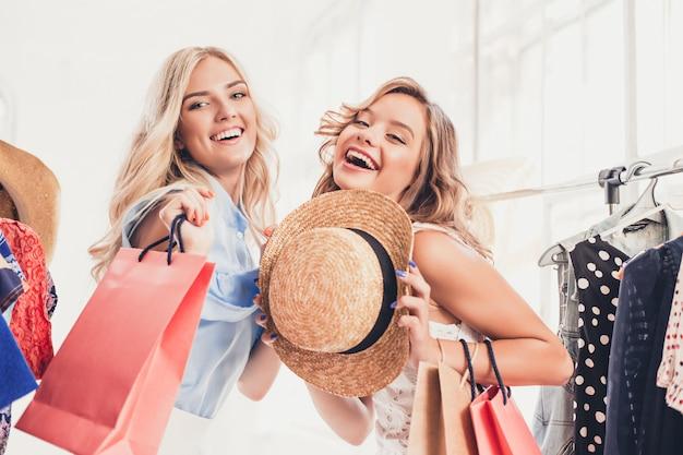 Le due giovani belle donne che guardano i vestiti e provano mentre scelgono in negozio
