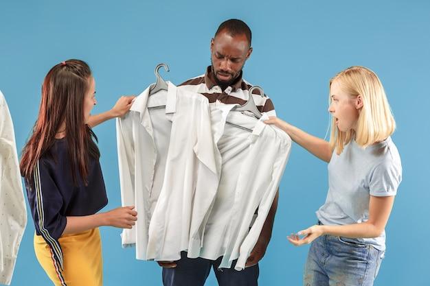 Le due giovani belle ragazze che guardano i vestiti e provano mentre scelgono in negozio