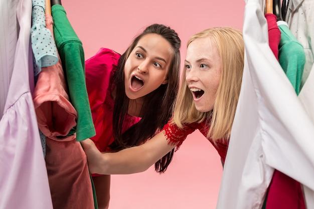 Le due giovani belle ragazze guardano i vestiti e provano mentre scelgono in negozio