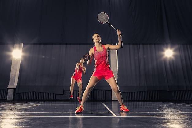 Le due giovani donne che giocano a badminton nello spazio della palestra. gioco di concetto in coppia
