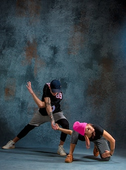 Le due giovani ragazze e ragazzi che ballano hip hop al blu
