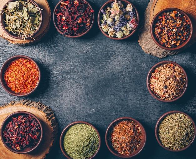 Le erbe del tè in ciotole con il piano di mozziconi di legno giacciono su uno sfondo scuro con texture. spazio per il testo
