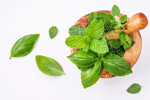 Le erbe fresche della medicina alternativa nel mortaio di legno hanno installato su fondo di legno bianco.