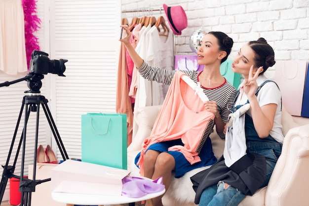 Le fashion blogger reggono due abiti colorati