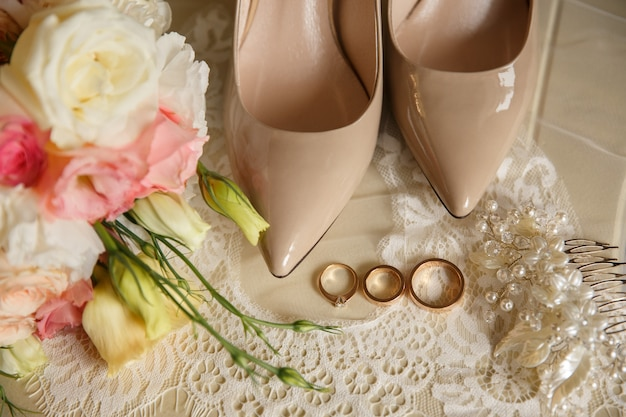 Le fedi nuziali si avvicinano alle scarpe nuziali sui tacchi alti e sul mazzo di nozze