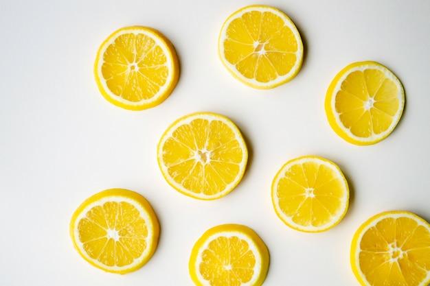 Le fette di limone si trovano a caso sulla superficie chiara del tavolo.