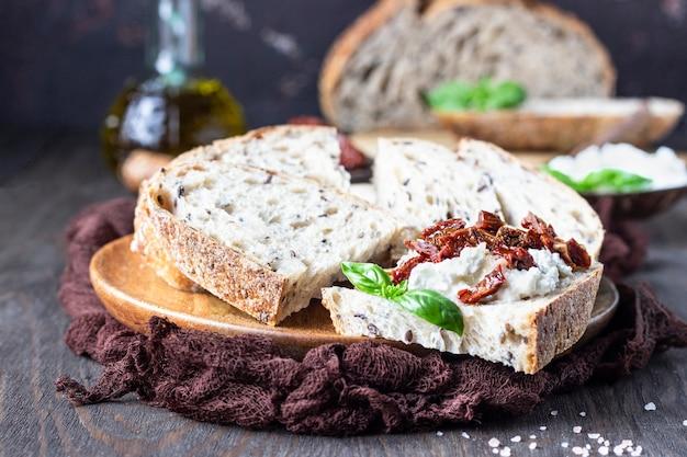 Le fette di pane con la ricotta, i pomodori seccati al sole ed il basilico sono servito sul tagliere di legno. bruschetta con ricotta, pomodori secchi e basilico.