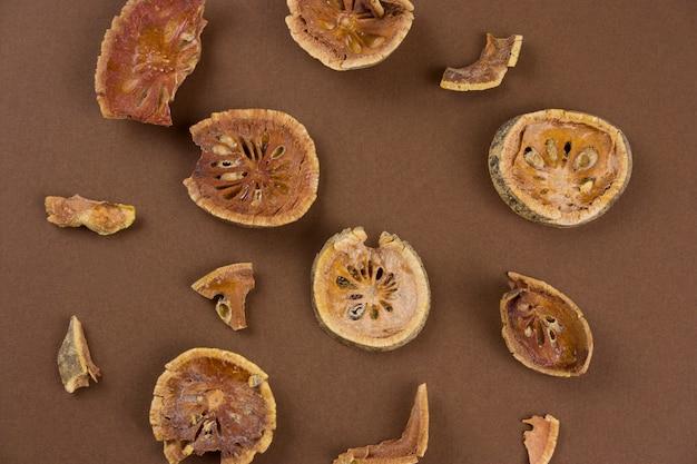 Le fette secche della frutta di bael di vista superiore (matum) su un fondo marrone