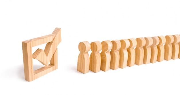 Le figure umane di legno stanno in fila accanto al segno di spunta di legno nella scatola. concetto di elezioni