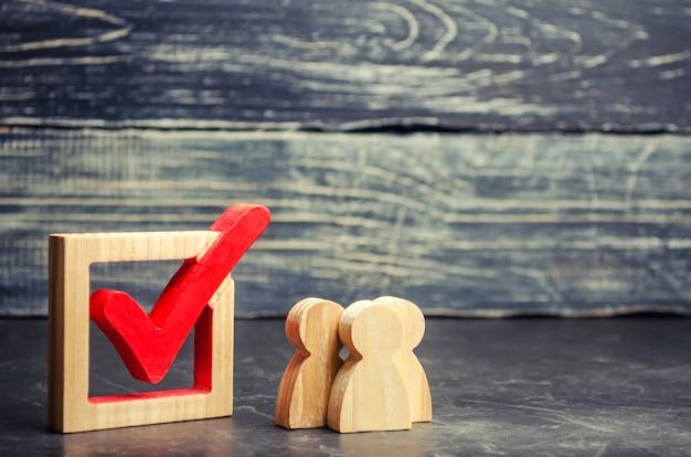 Le figure umane in legno stanno insieme accanto a un segno di spunta nella casella. il concetto di elezioni