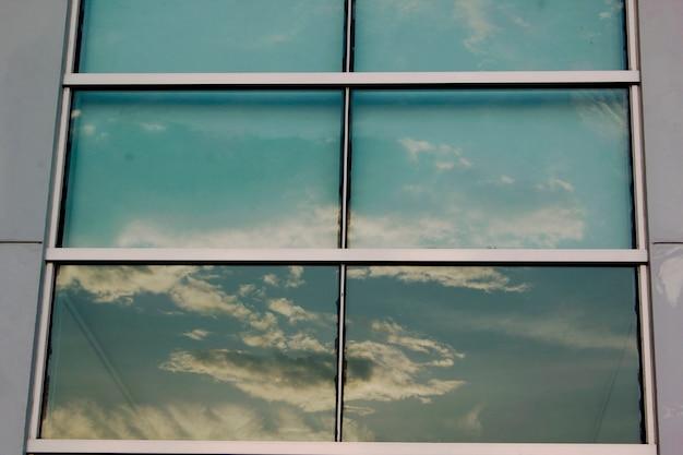 Le finestre di vetro riflettono l'ombra del cielo.