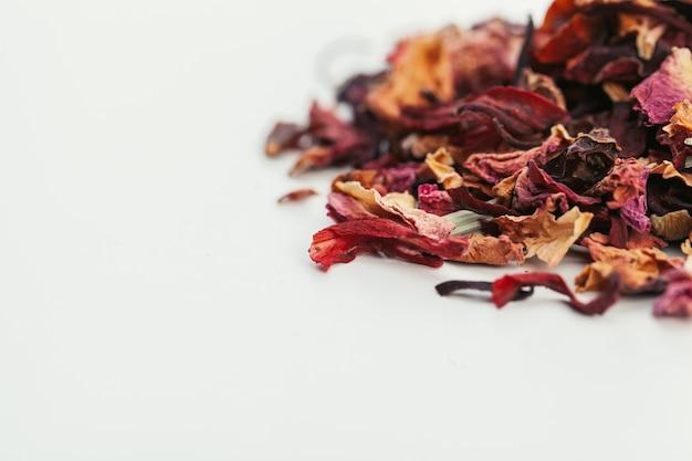 Le foglie di tè secche si chiudono su su bianco