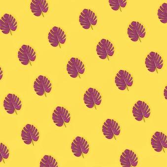 Le foglie tropicali di monstera della palma si trova su giallo