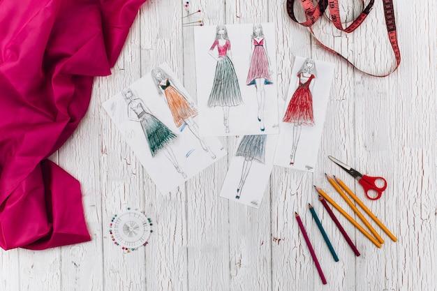 Le foto con modelli di abiti, stoffa rosa e altri accessori per l'artigianato si trovano sul tavolo