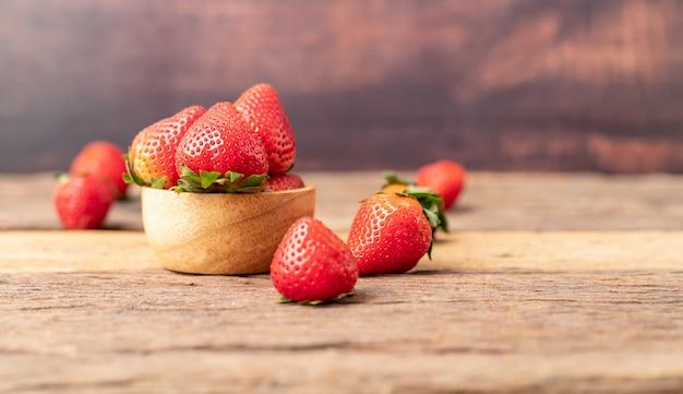 Le fragole mature di freschezza sono in una ciotola di legno disposta sul tavolo