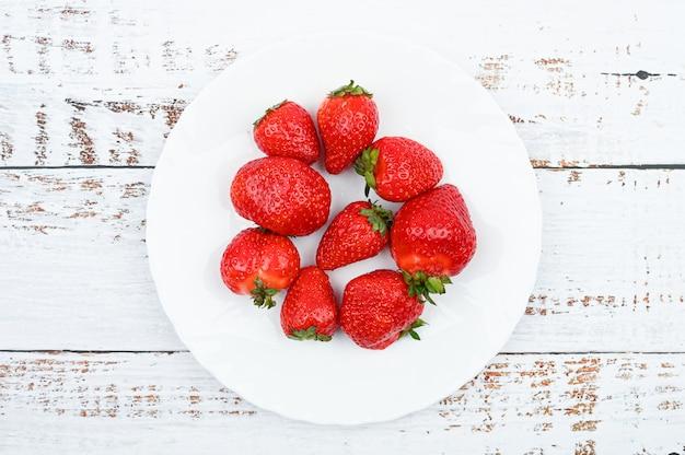 Le fragole rosse su un piatto bianco stanno su una tavola bianca di legno