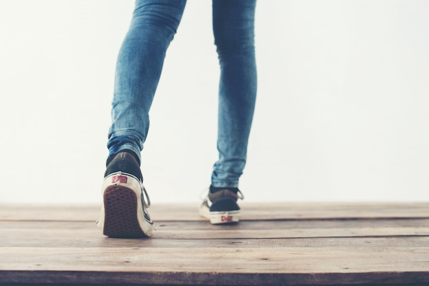 Le gambe che camminano all'indietro e scarpe blu