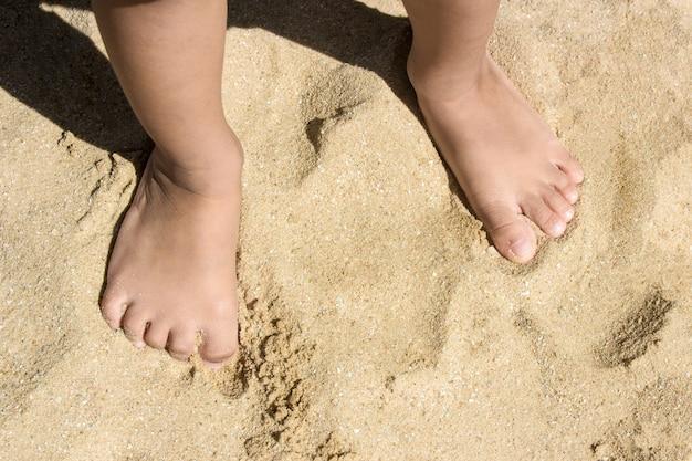 Le gambe dei bambini stanno sulla spiaggia con lo spazio della copia