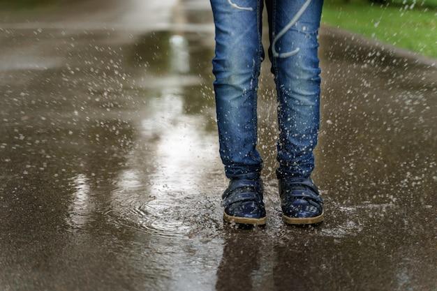 Le gambe del bambino in primo piano delle scarpe da tennis, il bambino salta in pozzanghere. salute, concetto di infanzia felice.