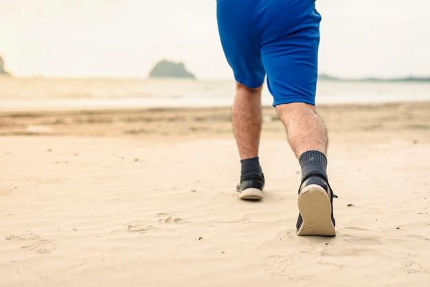 Le gambe del corridore dell'uomo che corrono si chiudono su sulla scarpa, uomini che pareggiano sulla spiaggia