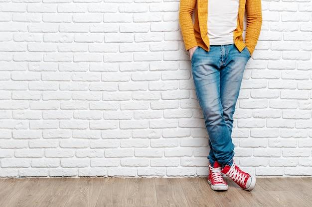 Le gambe del giovane uomo di moda in jeans e scarpe da ginnastica sul pavimento di legno