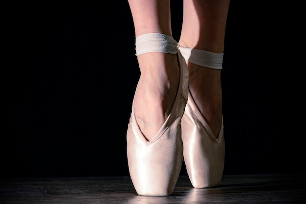 Le gambe della ballerina classica del primo piano nelle punte sul nero