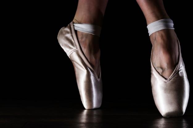 Le gambe della ballerina classica del primo piano nelle punte sul pavimento nero