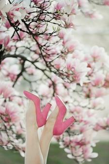 Le gambe della bella donna con le scarpe rosa sull'albero di magnolia in fiore
