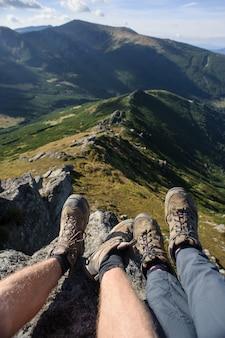 Le gambe della coppia sulla roccia in cima alla montagna
