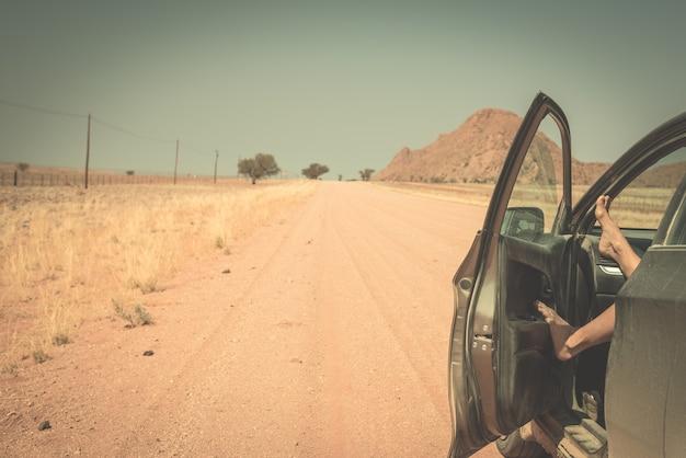 Le gambe della donna che pendono fuori dall'automobile che sta sulla strada della ghiaia nel deserto di namib