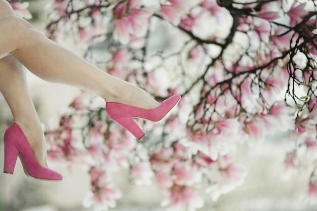 Le gambe della donna con le scarpe rosa sull'albero di magnolia in fiore