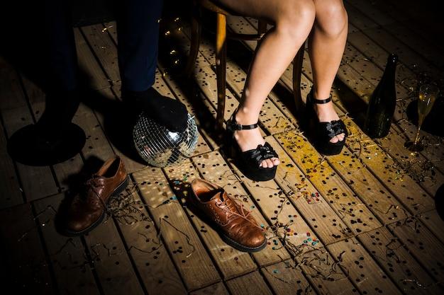 Le gambe della donna in scarpe vicino alla gamba dell'uomo sulla palla da discoteca vicino agli stivali