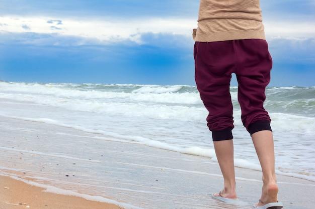 Le gambe della ragazza camminano sulla spiaggia