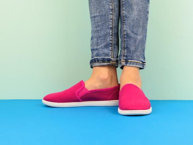 Le gambe della ragazza dei pantaloni a vita bassa in jeans sul pavimento blu dalla parete blu