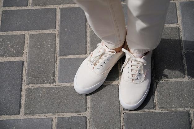 Le gambe della ragazza in nuove scarpe da ginnastica bianche e jeans