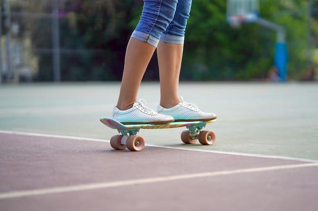 Le gambe della ragazza su uno skateboard