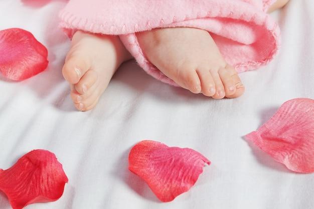 Le gambe di un bambino e petali di rosa. avvicinamento.