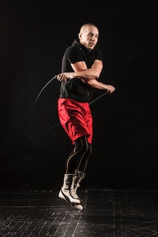 Le gambe di un uomo muscoloso con la corda per saltare