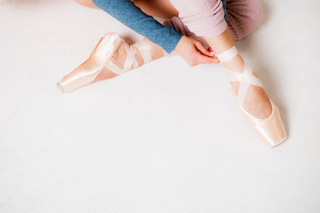 Le gambe di una ballerina in pointe calza il primo piano su una vista superiore del fondo bianco