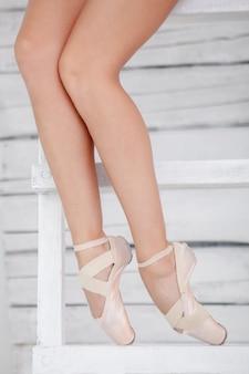 Le gambe di una ballerina su sfondo bianco