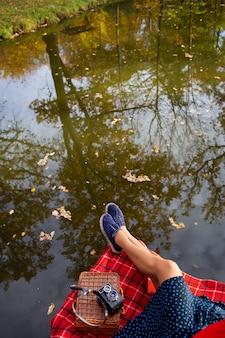 Le gambe di una bambina vicino al lago giacciono su un plaid rosso. bellissimo riflesso nell'acqua, foglie cadute sull'acqua. vista dall'alto