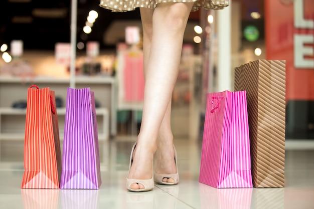 Le gambe di una giovane ragazza con sacchetti colorati