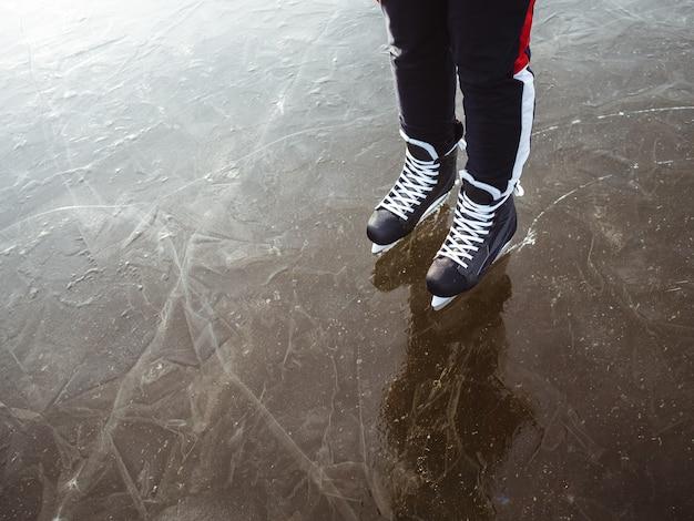 Le gambe di una ragazza in hockey nero pattina sul ghiaccio di un lago