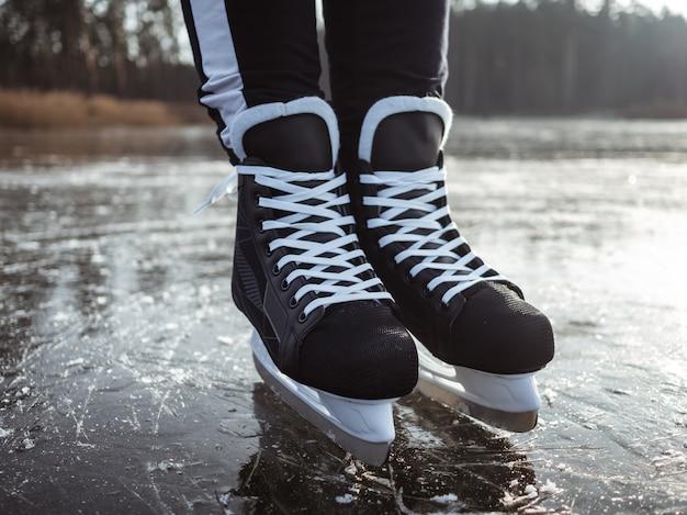 Le gambe di una ragazza in hockey nero pattina sul ghiaccio di un primo piano del lago. sullo sfondo una foresta