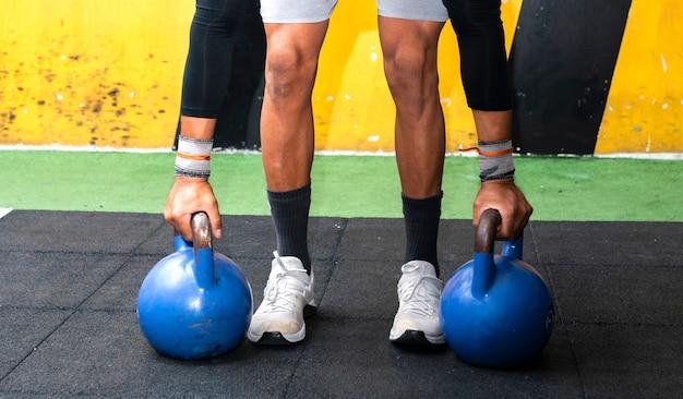 Le gambe e le mani dell'uomo tengono il kettlebell