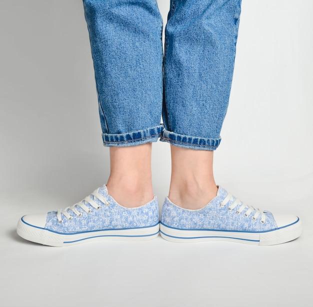 Le gambe femminili in jeans corti e scarpe da tennis stanno su un bianco